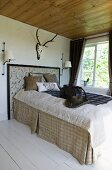 Stately bed with rustic bedspread in natural fibres below stag antlers