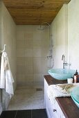 Shower head in narrow shower room with wooden ceiling; long wooden washstand with two glass washbasins in foreground