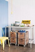 Old wooden crates on castors under simple console table in kitchen