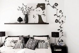 Double bed, feminine black and white wall decoration and photograph of Audrey Hepburn