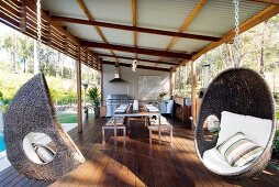 Roofed outdoor kitchen next to pool with long dining table and wicker hanging chairs