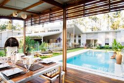 Dining table on roofed terrace with view of pool and luxurious, one-storey white house with pitch roof