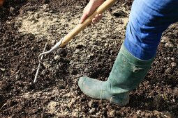 A lady wearing wellingtons mixing earth and sand together with a rake