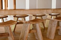 Carved wooden table and stools in beach house retreat, Indian state of Goa