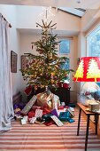 Traditionally decorated Christmas tree raised above mountain of presents in large bay window; lamp with glass balloon base and festive lampshade to one side