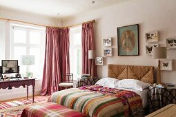 Butterfly collection on wall above wicker headboard of double bed, striped textiles and antique dressing table in front of lattice windows
