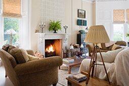 Gemütliches, helles Wohnzimmer mit Couchlandschaft im skandinavischem Stil und brennendem Kaminfeuer; im Vordergrund eine antike Tischlampe