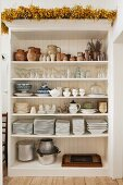 A variety of glassware, earthenware and crockery stored in an open white wooden shelf