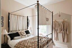 Imposantes Himmelbett aus Metall mit Leinenvorhängen und gemusterter Steppdecke in freundlichem Schlafraum