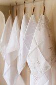 Weisse Baumwolltaschentücher an Wäscheklammern hängend