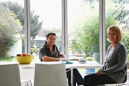 Woman and man taking a coffee break at a modern dining table in front of French doors