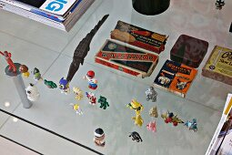 Small toy figures all in a row on a glass table