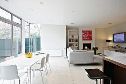 Modern dining table with white chairs in front of a bank of windows in a modern, open living room