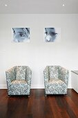 Modern armchairs with patterned upholstery fabric in front of a wall with portraits of children