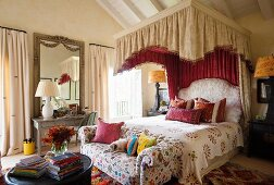 Canopied bed with Marrakech bedding in bedroom with button tufted sofa upholstered in Safi Suzani fabric. Both fabrics designed by Kathryn Ireland