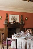 Dining table and wood fireplace in home of fabric designer Richard Smith in East Sussex
