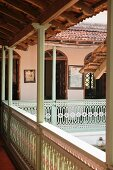 Roofed balcony with pale green and white carved balustrade encircling courtyard