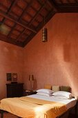 Double bed in bedroom painted rust red with brass pendant lamp hanging from exposed roof structure