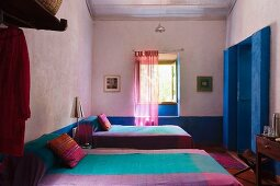 Colourful purple and turquoise bedspreads on twin beds in lilac bedroom with blue-painted entrance area