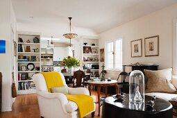 Offener Wohnbereich mit gemütlichem Polstersessel und mehreren Tischen und Sitzgelegenheiten