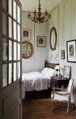 View through open door of bed against grey, wood-panelled walls of traditional bedroom