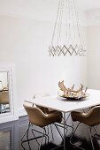 Designer pendant lamp above dining table with antlers in dish and fifties-style leather chairs on dark, glossy wooden floor