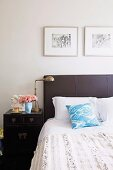 Double bed with upholstered headboard next to vintage bedside cabinet with brass table lamp
