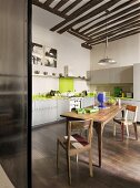 Large wooden table and chairs in kitchen with pale green cupboard doors and apple-green splashback
