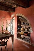 Shelving in niche in brick red dining room
