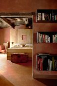 View past bookcase into bedroom of Mediterranean house