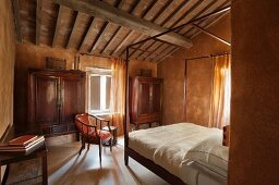 Four-poster bed and antique wardrobe in bedroom