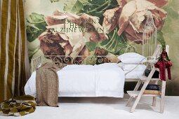 Verschnörkeltes Metallbett mit weißer Bettwäsche und Vintage Trittleiter vor Wand mit großflächigem Rosenmotiv