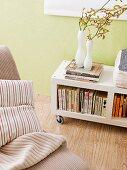 Blumenvasen auf Bücherregal mit Rollen vor pastellgrüner Wand und Kissen auf Sessel