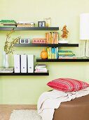 Books and box files on black floating shelves on pastel green wall and cushion on ottoman