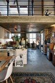 Loft-style interior with open-plan kitchen below mezzanine in roof space