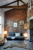 Modern lounge area with hare-shaped rug and brick wall in open-plan, rustic interior