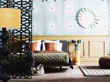 Standard lamp and partition to one side in front of double bed against half-height wood panelling below wallpaper with op art pattern