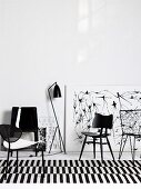 Black chairs from various eras on black and white striped rug in front of drawings leaning on wall