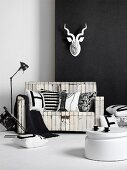Black and white, vintage-style furnishings - white coffee table in front of wooden bench with peeling paint below white paper hunting trophy on black wall