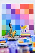 Figurine, books and pots of paint in front of colour sampler on wall