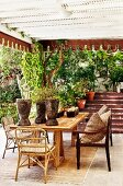 Roofed terrace seating area with potted plants on table in front of exterior steps