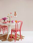 Pink-painted classic bentwood chair and white country-house table on straw rug
