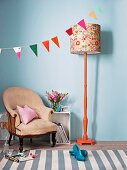 Bunting, standard lamp with orange-painted base and modern floral lampshade casually combined with vintage armchair against pale blue wall