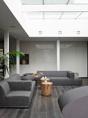 Atrium of modern, architect-designed house with grey sofa combination and white fitted cupboards with glossy doors