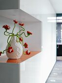 White, glossy, fitted cupboards with cut-out and orange stained glass shelf holding vase with crocheted cover and orange, crocheted flowers on green, wiggly stems
