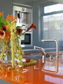 Designer kitchen with orange worksurface and bouquet of calla lilies in glass vase