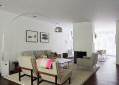 Polstergarnitur in offenem Wohnraum vor modernem Kamin und Designerleuchte mit Marmorsockel zur Tischbeleuchtung