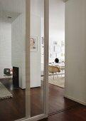 Geöffnetes Glastürelement läd in den offenen modernen Wohnraum mit zentralem Kamin ein, der dunkle Parkettboden verbindet die Wohnflächen