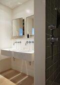 Designerbad mit zwei weißen Waschbecken, Wandarmaturen und Wandspiegelschränken, im Vordergrund eine geflieste Wand mit Duscharmatur