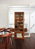 Holzvitrinenschrank steht vor Glaselement zum Treppenabgang auf dunklem Holzparkett, im Vordergrund Tisch mit eleganten dunklen Holzstühlen